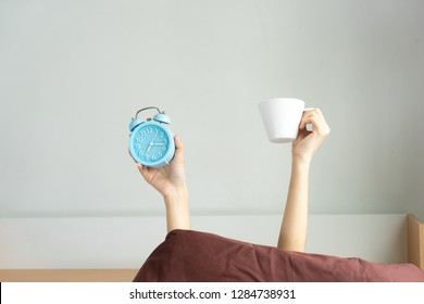 Woman arm hands holding coffee cup and blue alarm clock in on bed in bed room. Young girl with two hands holding blue clock and cup, drinking coffee after awaking. wake up with fun in morning concept.