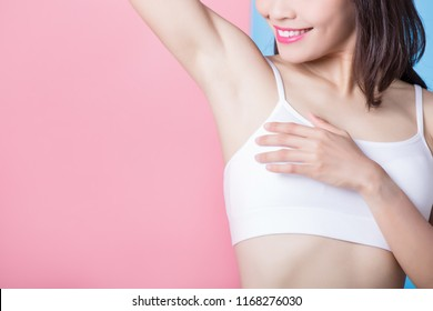 woman with armpit plucking on the pink background