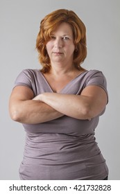 woman with arms crossed, with an angry stare