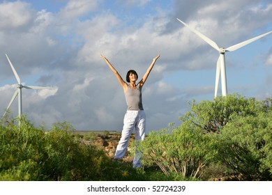 Woman with arms up next to wind turbines