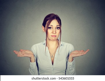 Woman with arms out shrugs shoulders so what I don't know isolated on gray wall background. Negative human emotion, facial expression