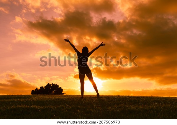 Woman with arms outstretched enjoying a beautiful sunset.