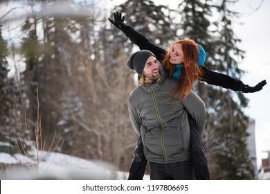 Woman with arms outstretched enjoying piggyback ride