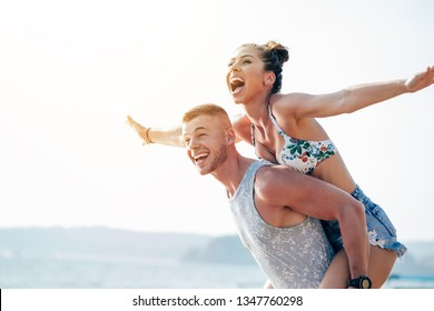 Woman with arms outstretched enjoying piggyback ride,Woman with arms outstretched enjoying piggyback ride