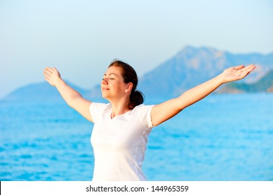 Woman with arms outstretched enjoying the sun by the sea