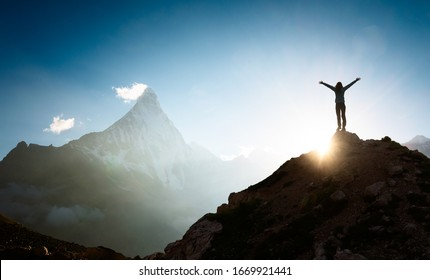 Woman with arms outstretched enjoying the sunrise in the mountains