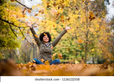 Woman with arms outstretched high up, outdoors.