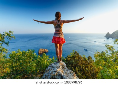 Woman with arms outstretched on a high rock above the blue sea. In the background there is a cliff of the Saint Phenomenon on the beach of the St. George Monastery in the Crimea. Summer. Freedom.Rest.