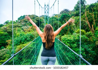 Woman with arms raised on hanging bridges of Costa Rica.