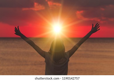 Woman with arms wide open looking at the sunset over ocean / sea.