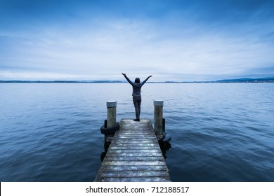 Woman with arms wide open. Wooden pier. Lake to the horizon.