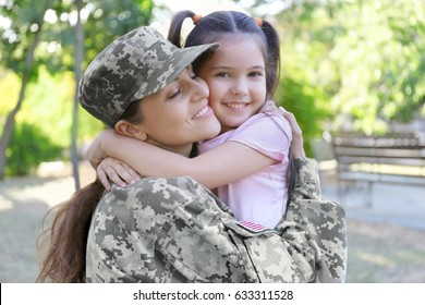 Woman in army uniform and her daughter in park