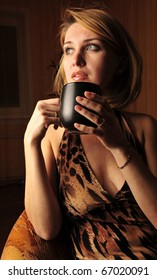 Woman with an aromatic coffee in hands sitting in armchair in dark room with romantic light