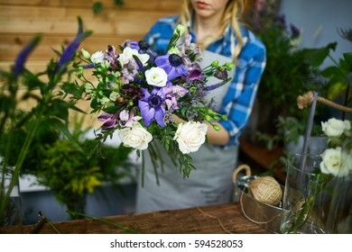 Woman arranging floral bouquet from fresh flowers