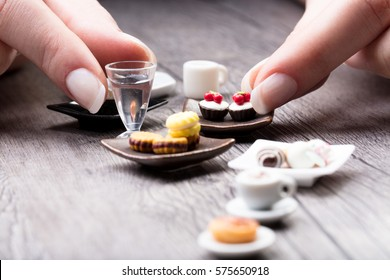 Woman arranging a miniature tea set and cookies with tiny iced cakes, parfait glass and cups of tea on a rustic wood table