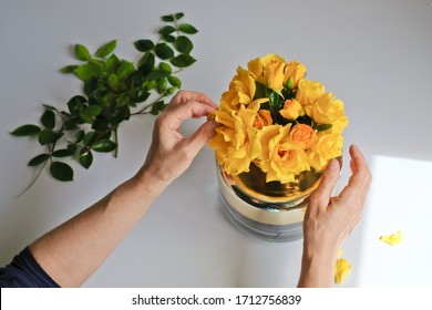 A woman arranging yellow roses in a vase