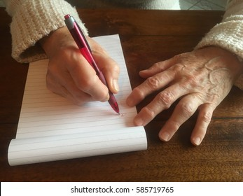 Woman with arthritis trying to write a letter