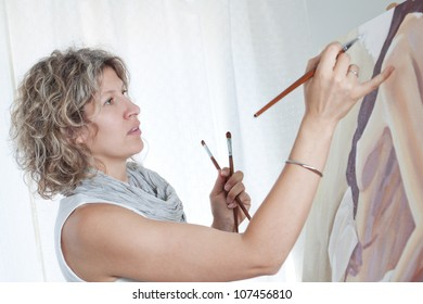 Woman artist draws a portrait of a woman.