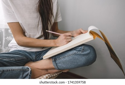 Woman artist draws in a sketchbook at home near the window, sitting on a chair in comfort and coziness, creativity. Drawing training.