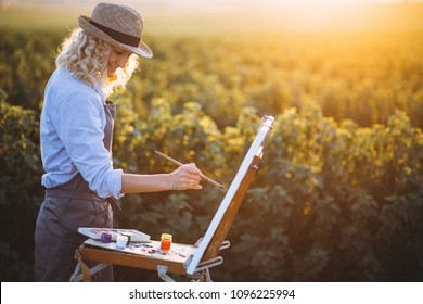 Woman artist painting with oil paints in a field