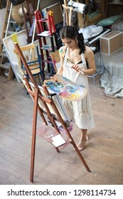 Woman artist painting picture in art studio. Female artist, drawing process.