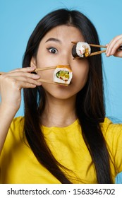 A woman of Asian appearance chopsticks seafood sushi and rolls