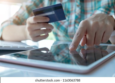 woman asian making online payment on mobile smart phone and laptop computer with credit card for shopping on onlines retail shop at home