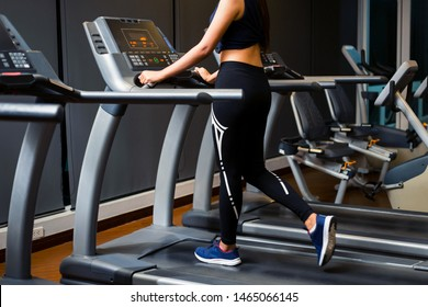 Woman asian wearing sportswear jogging on a treadmill at the gym.