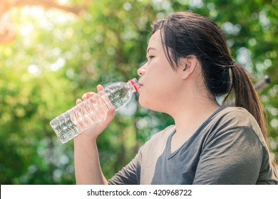 woman asian white long hair girl drinking water, drink water after work out exercising on morning park.