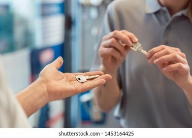 Woman asking locksmith to make a key copy, duplicate, close-up