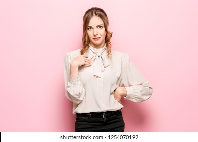 A woman asks who I am, showing on themselves fingers. Beautiful female half-length portrait isolated on pink studio backgroud. Young emotional surprised woman looking at camera.Human emotions, facial