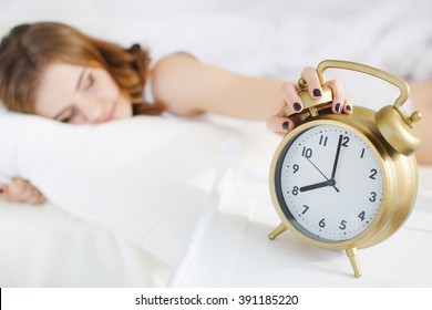 woman asleep in bed while her alarm shows the early time at home in bedroom. black alarm clock and woman in bedroom in morning.