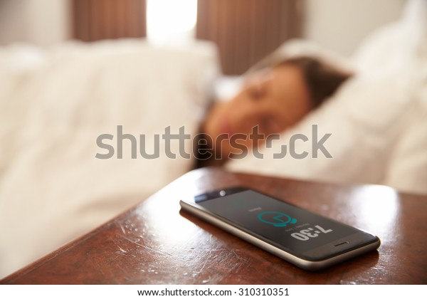 Woman Asleep In Bed Woken By Alarm On Mobile Phone