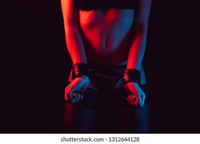 Woman ass. Arrested girl with handcuffs on black background. Sexual bdsm toy. Woman temptation. Outfit for playing bdsm games. Arrested lady with handcuffs. Temptation in society. Perfect sexy ass