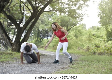 Woman assisting an injured man on the running track at garden. Couple has stumbled. Accident. stumble and fall while jogging.