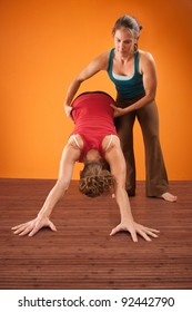 Woman assists her partner in a yogasana workout