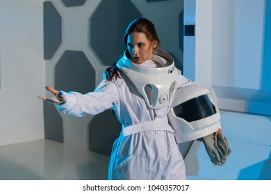 Woman astronaut on a futuristic spaceship. Holds the helmet in hand and points the hand somewhere