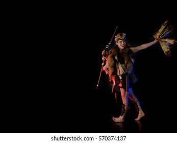 woman athlete in the Amazon costume posing on a black background in the scenic red and blue light.