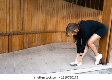 Woman athlete bent over to tie the laces on sneakers.