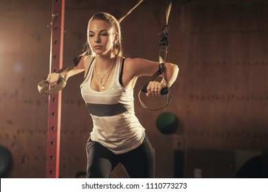 Woman athlete doing exercise in gym. Young attractive girl exercising with suspension trainer. Sportswoman working out in functional training. Workout. Sports.
