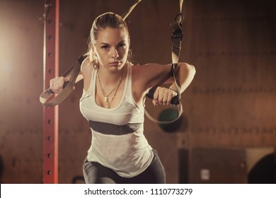 Woman athlete doing exercise with trx system in gym. Young attractive girl exercising with suspension trainer. Sportswoman working out in functional training. Workout. Sports fit.