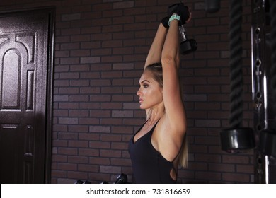 Woman athlete doing a french extensions with a dumbbell in the gym