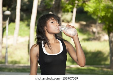 Woman athlete drinking water in the park