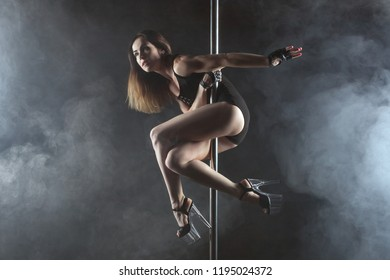 Woman athlete is engaged on the pylon, she performs gymnastic stunts.