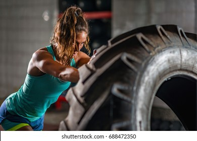 Woman athlete exercising with tire
