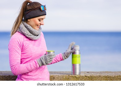 Woman athlete fit girl wearing warm sporty clothes outdoor in cold weather drinking hot tea from vacuum flask thermos, warming up. Sports, activities, hiking in winter or autumn time