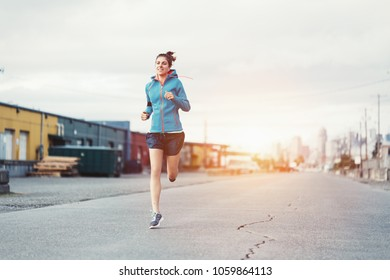 Woman athlete jogging in city industrial area