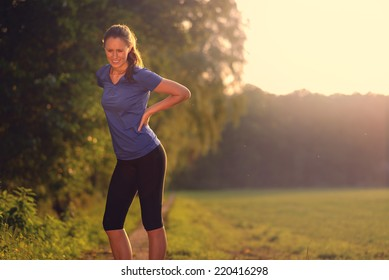 Woman athlete pausing to relieve her back pain holding her hand to her lower back with a grimace while out training in the countryside with copy space