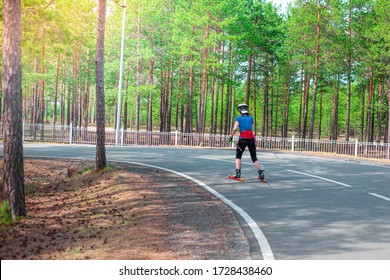 woman athlete is rolling down the track on roller skis, healthy lifestyle, summer skiing training