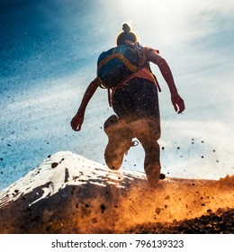 Woman athlete runs on a dirty and dusty ground with volcano on the background. Trail running athlete working out in the mountains